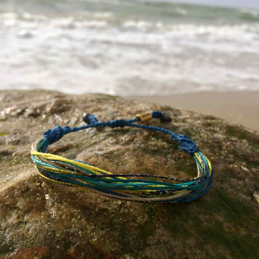 String Surfer Bracelet Blue Yellow Aqua Tan and Metallic Purple: Handmade on Martha's Vineyard Waxed Cord Sailor and Surf Bracelets by Rumi Sumaq